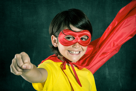 closed fist: Closeup of little boy in superhero costume posing isolated on blackboard. Smiling kid looking at camera with red mask. Cheerful cute boy wearing superhero costume with red cape flying with closed fist. Stock Photo