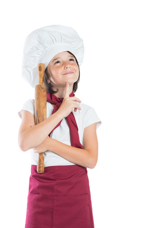 Closeup of boy dressed as chef thinking with hand on chin. Portrait of pensive young chef looking up. Smiling cute boy dressed as cook isolated on white background.