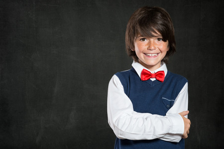 lovable: Closeup shot of little boy standing with armcrossed isolated on blackboard. Smiling cute male child with red papillon looking at camera. Lovable boy wearing waistcoat and red bow tie. Pretty boy with copy space.