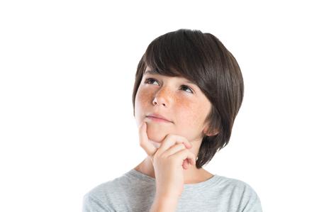 考えてかわいい男の子の肖像は、白い背景で隔離。少年と考えてのクローズ アップ ショットは、あごに手します。見上げるそばかすのある男性の子