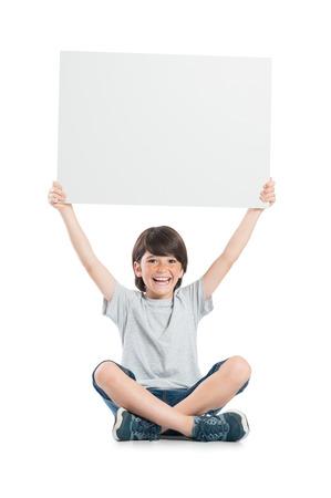 Niño pequeño sonriente sosteniendo pancartas aisladas sobre fondo blanco. Chico lindo feliz que sostiene el cartel en blanco sentado en el suelo blanco. Niño de risa que muestra signo blanco vacío.
