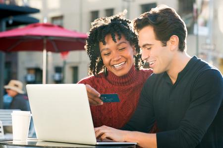 Mooie jonge verliefde paar online winkelen bij elkaar, terwijl de vrouw creditcard bedrijf en glimlachen. Portret van gelukkige paar betalen van rekeningen online met behulp van laptop en een creditcard. Gelukkig glimlachend paar met laptop en creditcard online kopen via e-commerce