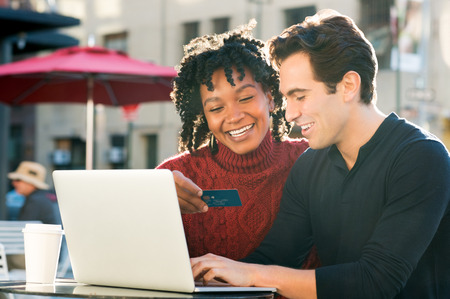 Beautiful young loving couple shopping online together while woman holding credit card and smiling. Portrait of happy couple paying bills online using laptop and credit card. Happy smiling couple with laptop and credit card buying online through ecommerce