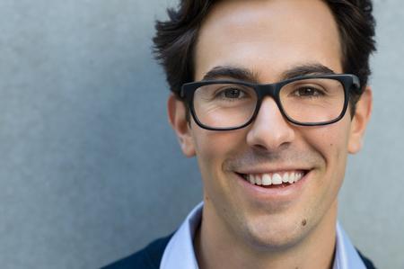 portrét: Mladý muž s úsměvem a při pohledu na brýle s fotoaparátem na sobě. Portrét šťastné pohledný mladý muž nosí brýle s šedým pozadím. Zblízka mladého chladné módní člověka s brýlemi a kopírování prostor.
