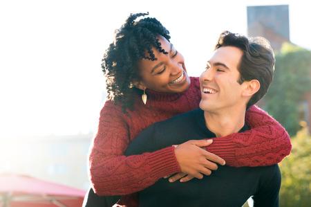 Portret van een gelukkige jonge paar genieten van de buitenlucht. Afrikaanse vrouw meeliften op zijn vriend en kijken naar elkaar. Jonge mens die vriendin meeliften rit en openlucht glimlachen. Stockfoto