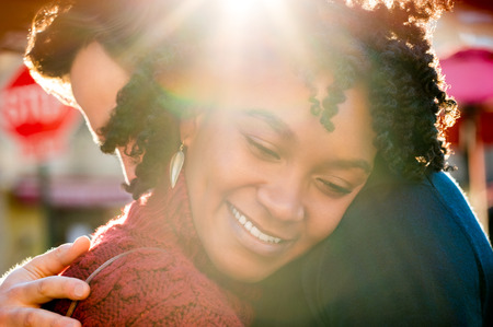 femme romantique: Heureux jeune homme africain femme �treindre dans une journ�e ensoleill�e. Close up visage d'une jeune fille embrassant son petit ami et souriant, les yeux ferm�s. Romantic couple heureux �treindre ext�rieur.