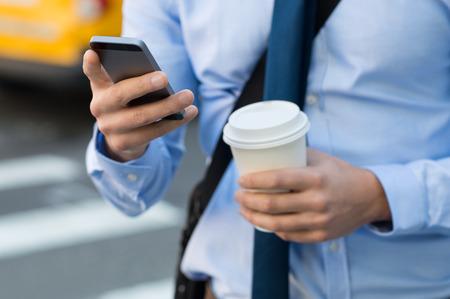 Close-up van een zakenman met behulp van mobiele telefoon en het bedrijf document kop. Close-up detail van een zakenman hand houden papieren beker en met behulp van een smartphone tijdens het lopen op de weg. Mens die op het werk. Stockfoto