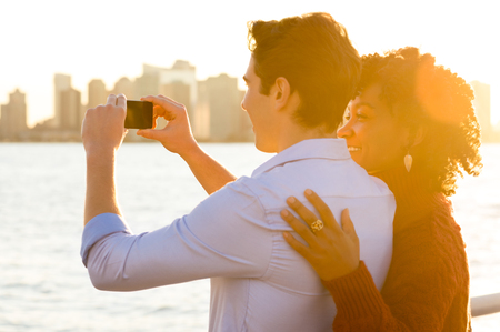 river side: Romantic couple tourists taking photo and having fun. Young happy couple taking photo of the river and skyscrapers with smartphone. Happy young couple embracing and taking photo at river side during sunset. Stock Photo