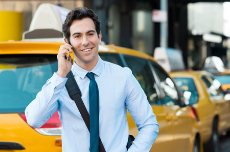 phone business: Young businessman talking on smartphone. Happy young casual professional businessman using cell phone outdside, in a city centre. Portrait of a handsome young man talking on the phone with yellow taxi in background.