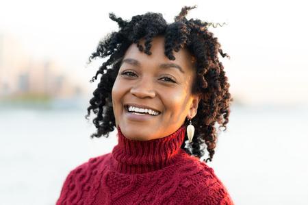 일몰 동안 강 측면에 서있는 아프리카 여자의 초상화를 닫습니다. 행복 한 젊은 아프리카 찾고 카메라의 초상화입니다. 아프리카 여자 야외 카메라에