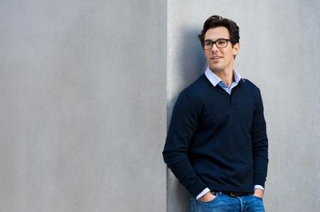 hombre de negocios joven, apoyado en una pared gris que lleva gafas. hombre joven y guapo en el pensamiento casual con las manos en el bolsillo. Retrato de hombre sonriente pensativa con las lentes de pensamiento, con copia espacio gris.