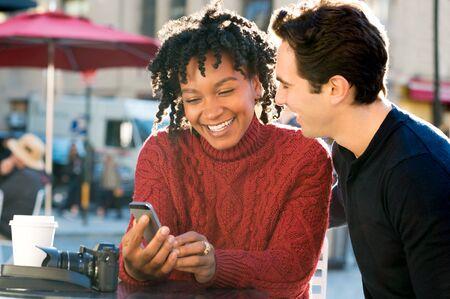 Portret van gelukkige jonge paar zitten lawaai buiten de kantine met smartphone. Close-up van gelukkige jonge paar lacht en kijkt naar de mobiele telefoon zittend op tafel in een koffiebar. Glimlachend paar met koffie en kijken naar de telefoon.