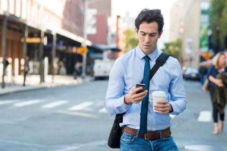 Biznesmen za pomocą smartfona i trzymając kubek papierowy ina miejskiej sceny. Zmartwiony biznesmen w chodzeniu na drodze i wiadomości z telefonu. Młody mężczyzna tekst wiadomości przez telefon komórkowy podczas spaceru na ulicy w centrum miasta.