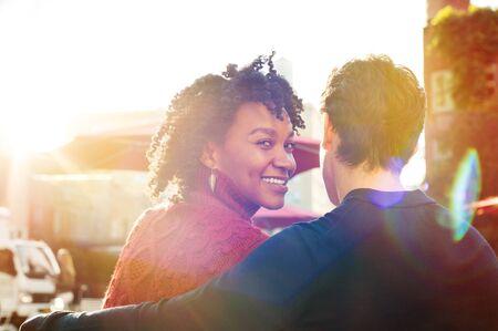 persona sentada: Mujer africana feliz y joven se sientan en el banquillo, mientras mira a la cámara en un café. Cierre de amantes de la pareja sentada en un momento de la cafetería y el gasto. Mujer sonriente joven que se sienta con un amigo en un café y mirando a la cámara.
