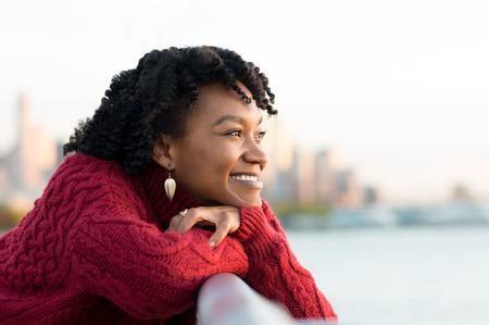 mujer pensando: Cerca de retrato de una joven Africana feliz apoyado en la barandilla de un puente cerca del río. joven Africana feliz en la orilla del río pensando en el futuro. niña pensativa mirando al otro lado del río en la puesta del sol sonriendo. Foto de archivo