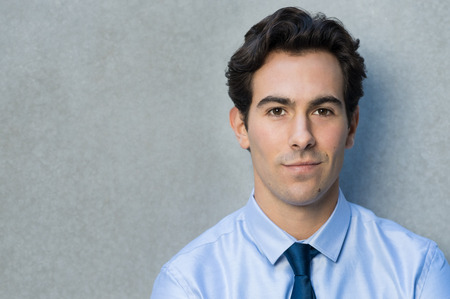 företag: Glad ung affärsman lutad mot grå vägg. Porträtt av en flinande affärsman med blu skjorta och slips tittar på kameran. Närbild på en vacker stolt ung man ler med kopia utrymme. Stockfoto