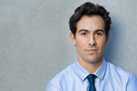 joven hombre de negocios feliz que se inclina contra la pared gris. Retrato de un hombre de negocios sonriendo con la camisa azul y corbata mirando a la cámara. Primer plano de un hombre joven y guapo sonriendo orgullosa con copia espacio.