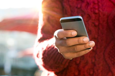 manos: Cierre de mensaje de texto escribiendo a mano de una mujer joven en su tel�fono inteligente. joven Africana que est� escribiendo en el tel�fono m�vil de pantalla t�ctil. Primer plano de la mano femenina que los mensajes de texto de un mensaje telef�nico al aire libre.