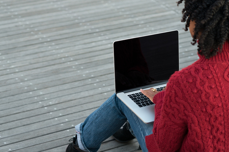 adult student: Rear view of young african woman sitting on stairs outdoor and working on laptop. Woman in casual sitting on wooden floors with laptop. Female hands typing on keyboard on her laptop outdoor.