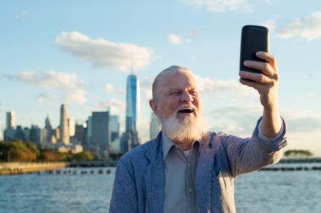 Glücklich lächelnd älterer Mann eine selfie in einem schönen Tag an der Flussseite nehmen. Ältere gesunder Mann genießt den Ruhestand. Lässige freudige Großvater ein selfie mit den Wolkenkratzern im Hintergrund bei Sonnenuntergang nehmen.