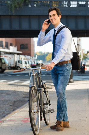 phone business: Businessman talking on cell phone holding his cycle on the footpath. Young cheerful businessman in standing with bicycle and using phone to go to office. Pleasant joyful man holding bicycle and talking on mobile phone.