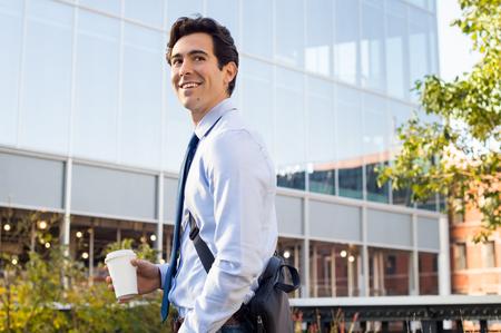 행복 한 젊은 사업가 걷고, 노트북 가방, 커피 종이 컵을 들고. 배경에 현대적인 건물과 멀리 찾고 만족 된 사업가. 행복 한 미소 사람 종이 컵에 걸릴