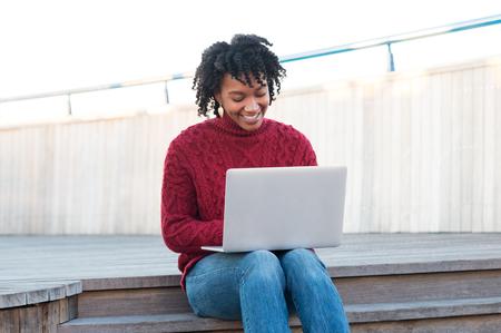 black girl: Junge afrikanische Frau sitzt auf hölzernen Treppen im Freien und am Laptop. Glückliche lächelnde junge Frau E-Mail auf dem Computer zu überprüfen. Glücklich Student auf der Terrasse sitzen und in einem hellen sonnigen Tag auf dem Laptop zu studieren.