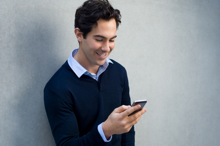 young business: Close up of a young man leaning against a grey wall using mobile phone. Portrait of a happy business man holding a smartphone. Man in casual typing and reading a message on cell phone with copy space.