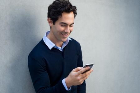 Primer plano de un joven apoyado contra una pared gris que usa el teléfono móvil. Retrato de un hombre de negocios feliz celebración de un teléfono inteligente. El hombre en la tipificación casual y lectura de un mensaje en el teléfono celular con copia espacio.