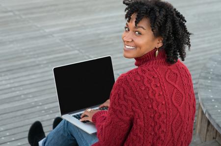negras africanas: Mujer africana joven que se sienta en las escaleras de madera al aire libre y de trabajo en la computadora portátil. casual mujer feliz sentado en el suelo de madera con el ordenador portátil y mirando a la cámara. Sonriendo Adultos que estudia en el PC.