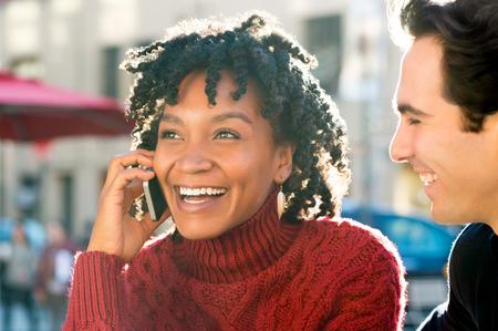 afroamericanas: Cierre de tiro de una mujer joven africano sentado con el amigo, hablando por teléfono. joven pareja disfrutando de una buena noticia recibida a través del teléfono. Muchacha de risa que tiene una agradable conversación en el teléfono móvil.