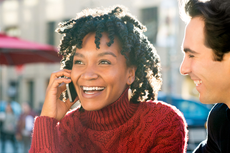 african american: Close up shot of a young african woman sitting with friend talking on phone. Young couple enjoying a good news received over phone. Laughing girl having a nice conversation on mobile phone.