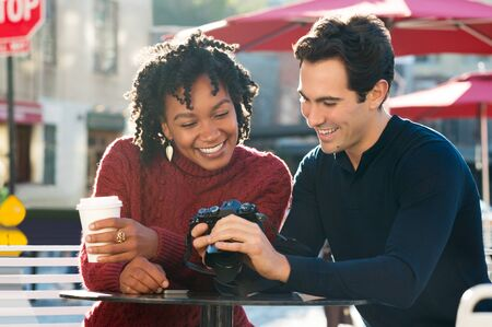 hombres jovenes: Happy young tourist couple looking at pictures in their camera in a cafe. A smiling couple looking at their photos on the screen of their camera in the cafe outdoor. Joyful multi ethnic couple sitting at cafeteria using a camera with coffee paper cup in h