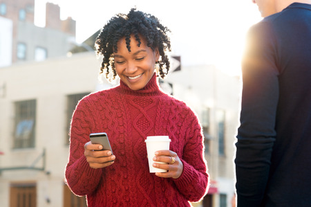 text: Young woman standing with friend texting on the phone and holding a take away paper up of coffee. African girl with paper cup writing text message with smart phone while walking on road. African woman with cellphone and coffee smiling.