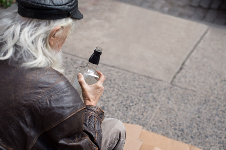 alcoholic man: Portrait of a poor senior man sitting on cardboard with a bottle of whiskey. Old drunk man with white beard holding a bottle of whiskey. Close up of homeless sitting on cardboard in a drunken state and drinking whiskey. Stock Photo