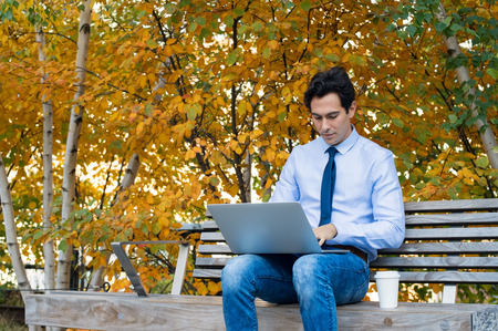 man sit: Businessman using laptop in the park in a sunny autumn day with a cup of coffee. Young businessman sitting on the park bench with laptop on his lap and checking the email. Freelancer man sitting on bench of a park and working on laptop very seriously.