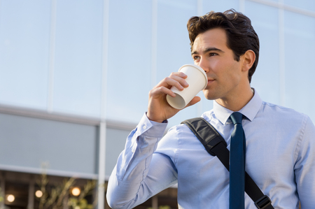 man drinking coffee: Successful young businessman drinking a take away coffee outside office. Businessman drinking coffee and thinking about his future. Happy ambitious man drinking an hot coffee with a paper cup in front of the modern building. Stock Photo