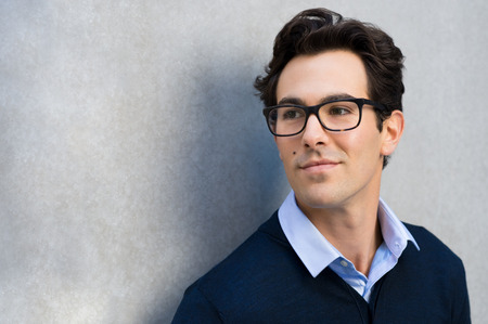 Smiling guy wearing glasses looking away and leaning on grey wall. Handsome young business man in casual wearing goggles and thinking. Portrait of young businessman with eyeglasses thinking about his carrer with copy space.
