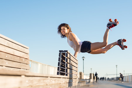 balancing act: Happy young joyful woman doing a balancing act wearing rollerskates. Young woman in skates jumping with the support of a bench. Beautiful young happy woman wearing roller blades doing a stunt. Stock Photo