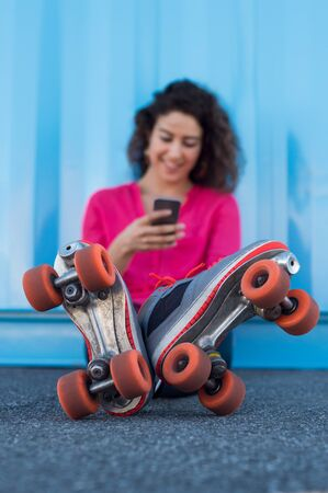 rollerskates: Woman sitting on ground wearing rollerskates holding a smartphone. Young woman reading a text message and smiling. Happy young woman sitting and wearing rollerskates while typing on smart phone.