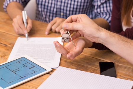 key: Happy young couple getting keys of their new house. Close up of female hand receiving keys from house broker. Closeup of the hand of a real estate agent who give the house keys to a woman while her boyfriend signing a contract.