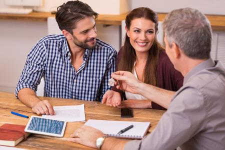 Pares que reciben felices jóvenes llaves de la casa de agente de bienes raíces. Que da claves de la nueva casa de la joven pareja. Sonriendo par de firmar el contrato financiero por hipoteca. Foto de archivo