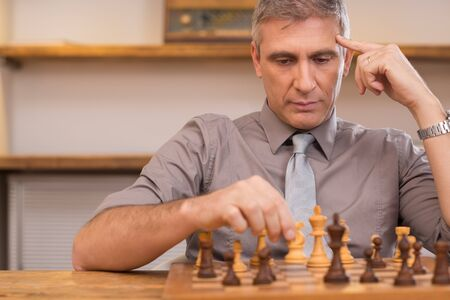 Mature man thinking while playing chess. Portrait of concentrated businessman playing chess. Senior chess player deeply concentrated on the chessboard at office. Business man moving chess figure, strategy concept.