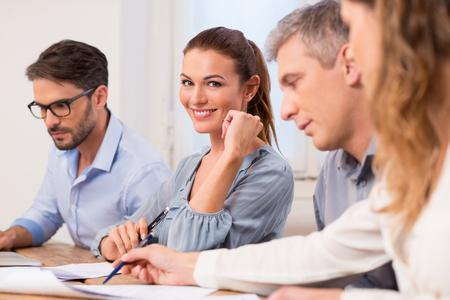 Bir toplantı sırasında kameraya bakarak mutlu genç işkadını portre. Bir toplantıda otururken güzel işkadını. Tartışma ve ofiste bir toplantı sırasında birlikte çalışan bir satırda Businesspeople.