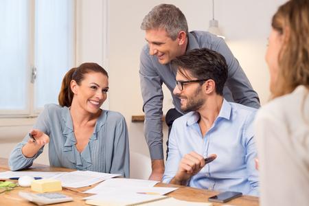 Gelukkig ondernemers tijdens een vergadering. Lachend zakelijke teamwerk na het krijgen van een deal. Groep gelukkige jonge mensen uit het bedrijfsleven in een vergadering op kantoor met een manager.