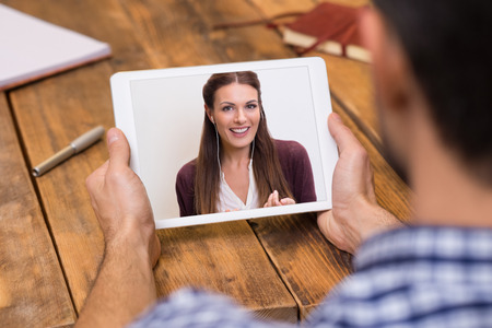 Closeup of a woman talking through video chat on tablet. Young man communicating with his girlfriend on tablet in video chat. Young man looking at screen of tablet and talking with a woman trought webcam. Stock Photo