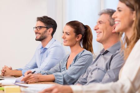 Gente di affari felice in fila ad ascoltare un seminario in ufficio sala riunioni. Un gruppo di uomini d'affari seduti come pannello per la conduzione colloquio di lavoro. Felice team di giovani uomini d'affari colpito da una presentazione. Archivio Fotografico