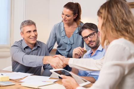 Apretón de manos para sellar un acuerdo tras una reunión de reclutamiento del trabajo. Dos hombres de negocios exitosos agitando las manos delante de sus colegas. hombre de negocios maduro estrechar la mano para sellar un acuerdo con la empresaria en una oficina moderna.