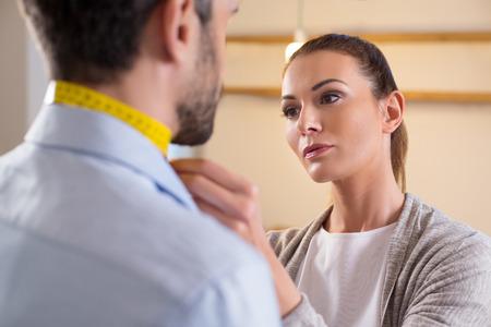 Portret projektant mody pomiaru szyi mężczyzny w studiu. Młoda kobieta krawcowa na krawców podejmowania środków. Krawiec pomiaru wielkości na szyte na miarę garnitur dla młodego człowieka biznesu.