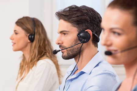Happy young employees working in call centre. Portrait of a young attractive telephone operator working in a call center. Customer service representative wearing a headset at the office.